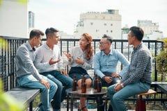 Amigos étnicos de conversa com cerveja no balcão imagens de stock