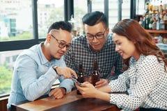 Amigos étnicos de relaxamento com cerveja e telefone imagens de stock royalty free