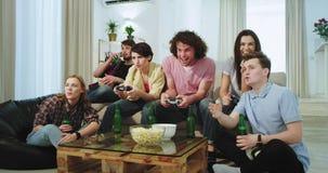 Amigos étnicos grandes do sofá nos multi que jogam em um jogo de vídeo na tevê dois deles a senhora era o vencedor o indivíduo do filme