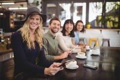Amigos étnicos multi sonrientes que se sientan con las tazas de café y los teléfonos móviles en la tabla Imagen de archivo libre de regalías