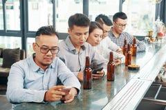 Amigos étnicos separados com os telefones na barra foto de stock royalty free