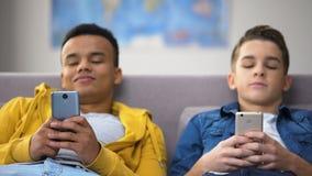 Amigos adolescentes afro-americanos e caucasianos que surfam em locais com índice adulto video estoque