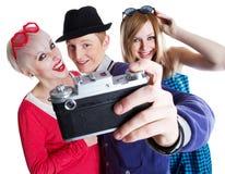Amigos adolescentes alegres con la cámara de la foto Fotografía de archivo libre de regalías