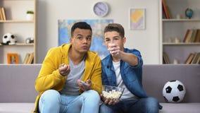 Amigos adolescentes ansiosos que miran el partido de fútbol en la TV y que comen ocio de las palomitas almacen de video