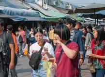 Amigos adolescentes asiáticos que caminan y que comen un poco de comida y que beben el zumo de fruta Foto de archivo libre de regalías