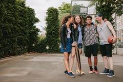 Amigos adolescentes con el monopatín y el baloncesto Fotografía de archivo libre de regalías