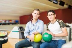 Amigos adolescentes con las bolas de bolos que se sientan en club Imagen de archivo libre de regalías