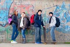 Amigos adolescentes con los bolsos de escuela y los patines Fotos de archivo libres de regalías