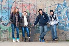 Amigos adolescentes con los bolsos de escuela y los patines Imágenes de archivo libres de regalías