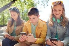 Amigos adolescentes con smartphone y los auriculares Fotografía de archivo