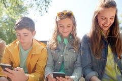 Amigos adolescentes con smartphone y los auriculares Foto de archivo libre de regalías