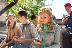 Amigos adolescentes con smartphone y los auriculares Imagen de archivo libre de regalías