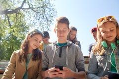 Amigos adolescentes con smartphone y los auriculares Fotografía de archivo libre de regalías