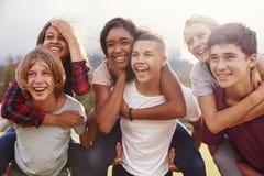 Amigos adolescentes de la escuela que se divierten que lleva a cuestas al aire libre foto de archivo libre de regalías