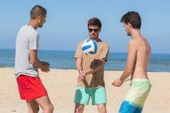 Amigos adolescentes del grupo que juegan a voleibol en la playa Fotos de archivo