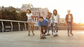 Amigos adolescentes diversos que montan en los monopatines y los rodillos fotos de archivo