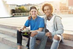 Amigos adolescentes diversos que se sientan al aire libre con los patines fotografía de archivo