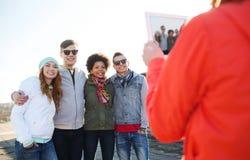 Amigos adolescentes felices con la fotografía de la PC de la tableta Fotos de archivo libres de regalías