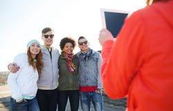 Amigos adolescentes felices con la fotografía de la PC de la tableta Foto de archivo libre de regalías