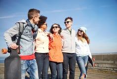 Amigos adolescentes felices con longboards en la calle Imagenes de archivo