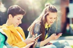Amigos adolescentes felices con los artilugios al aire libre Fotos de archivo