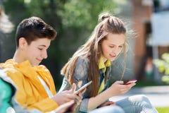 Amigos adolescentes felices con los artilugios al aire libre Fotos de archivo libres de regalías