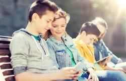 Amigos adolescentes felices con PC de la tableta al aire libre Fotografía de archivo