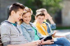 Amigos adolescentes felices con PC de la tableta al aire libre Imágenes de archivo libres de regalías