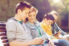 Amigos adolescentes felices con PC de la tableta al aire libre Foto de archivo