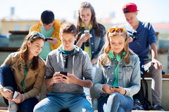Amigos adolescentes felices con smartphones al aire libre Foto de archivo
