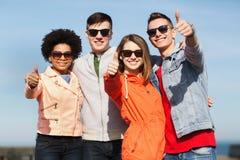 Amigos adolescentes felices en las sombras que abrazan al aire libre Imagen de archivo libre de regalías