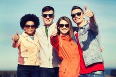 Amigos adolescentes felices en las sombras que abrazan al aire libre Foto de archivo libre de regalías