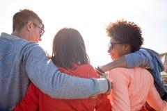 Amigos adolescentes felices en las sombras que abrazan en la calle Fotos de archivo libres de regalías