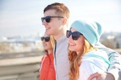 Amigos adolescentes felices en las sombras que abrazan en la calle Foto de archivo