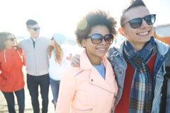 Amigos adolescentes felices en las sombras que abrazan en la calle Imágenes de archivo libres de regalías