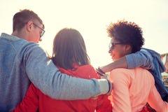 Amigos adolescentes felices en las sombras que abrazan en la calle Foto de archivo libre de regalías