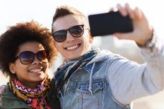 Amigos adolescentes felices en las sombras que toman el selfie Imagen de archivo libre de regalías