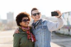 Amigos adolescentes felices en las sombras que toman el selfie Imágenes de archivo libres de regalías