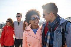 Amigos adolescentes felices en sombras que hablan en la calle Fotografía de archivo