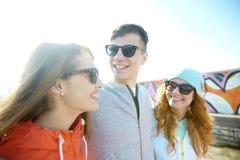 Amigos adolescentes felices en sombras que hablan en la calle Imagen de archivo