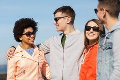 Amigos adolescentes felices en sombras que hablan en la calle Foto de archivo