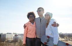 Amigos adolescentes felices en sombras que hablan en la calle Foto de archivo libre de regalías