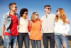 Amigos adolescentes felices en sombras que hablan en la calle Fotos de archivo libres de regalías