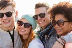 Amigos adolescentes felices en sombras que hablan en la calle Fotografía de archivo libre de regalías