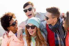 Amigos adolescentes felices en sombras que ríen al aire libre Imagenes de archivo