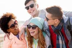 Amigos adolescentes felices en sombras que ríen al aire libre Fotografía de archivo
