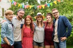 Amigos adolescentes felices que abrazan en el jardín del verano Fotografía de archivo libre de regalías