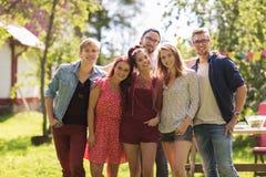 Amigos adolescentes felices que abrazan en el jardín del verano Imágenes de archivo libres de regalías