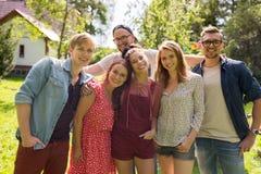 Amigos adolescentes felices que abrazan en el jardín del verano Imagen de archivo