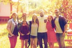 Amigos adolescentes felices que abrazan en el jardín del verano Fotografía de archivo